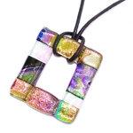 Felgekleurde ketting hanger met helder glas dat felgroen kleurt op een donkere ondergrond.