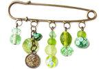 Handgemaakte kiltspeld in brons met groene kralen en een bedel van een muntje!
