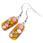 Lange gele glazen oorbellen met roze en gele millefiori bloemen.