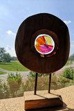 Houten object met glaskunst in rood, paars, roze, oranje en geel glas.