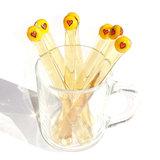 Helder amber geel glazen roerstaafje met rood hartje in het glas.