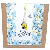 Vrolijke wenskaart met een glazen bijtje. Luxe dubbele kraft kaart met bloemen motief en een glazen bij om cadeau te geven.