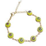 Goudkleurige RVS/edelstaal armband met prachtige gele millefiori bloemen.