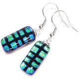 Lange glazen oorbellen van prachtig blauw-groen glas met zwart patroon.