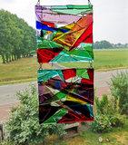 Glazen raamhanger gemaakt van helder paars, rood, blauw en groen gekleurd glas.