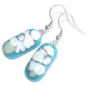 Handgemaakte lange lichtblauwe oorbellen met grijs-ivoorwitte accenten.