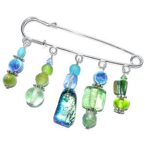 Handgemaakte grote speld/broche met diverse blauwe en groene kralen. Prachtige keramiek kralen, edelsteen kralen, parels, schel