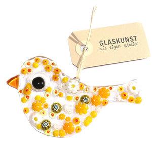 Glazen vogel van helder glas met gele en witte millefiori bloemen.