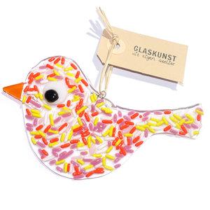 """Heldere glazen vogel hanger met roze, oranje, gele en witte """"sprinkles""""."""