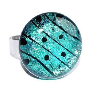 Edelstaal ring met glasfusing van groen en zwart glas met een patroon van stippen en strepen.