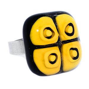 RVS edelstaal ring met glazen cabochon van zwart glas met gele vierkante figuren.