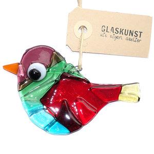 Kleurrijke glazen vogel hanger van rood, groen, blauw, paars en geel glas.