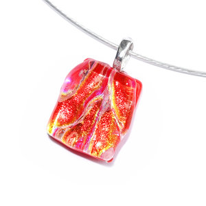 Kleine rode glazen hanger van opaal rood glas met helder dichroide glas in oranje-groen-gele accenten.