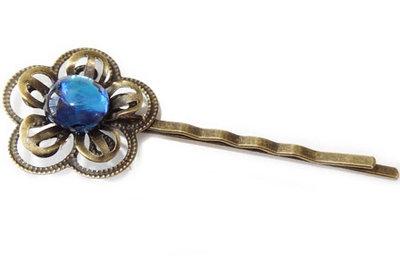 Bronskleurig haarschuifje met een blauwe petrol-kleurige glazen cabochon