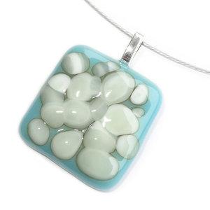 Handgemaakte glazen hanger van lichtblauw glas met ivoor-witte en grijze effecten.