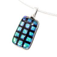 Kleine hanger van blauw/groen glas met zwart patroon. Glazen hanger voor aan een ketting.